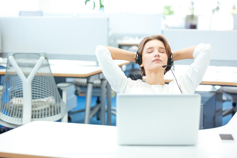 Carefree pretty woman sitting and relaxing on workplace in office stock image