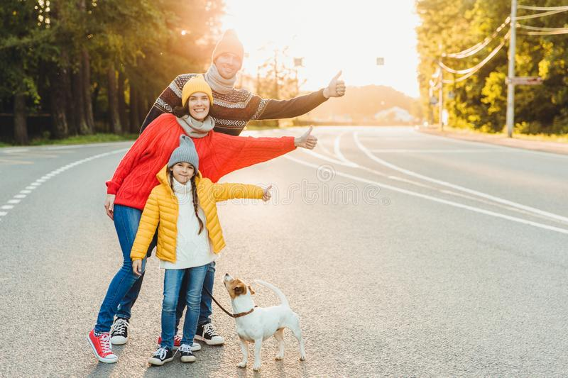 Carefree relaxed friendly family walk on road in countryside with dog, raise thumbs with enjoyment, wear warm clothes and sport sh royalty free stock photo