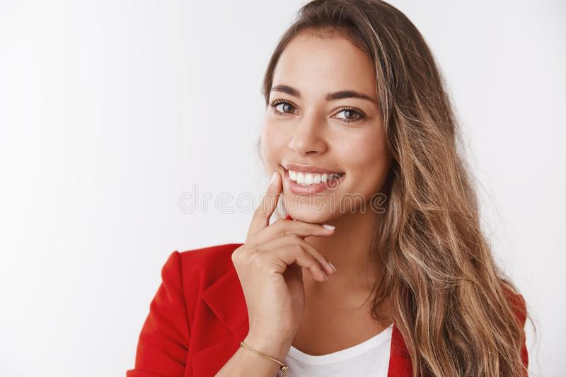 Carefree successful female entrepreneur giving lecture how become confident businesswoman smiling broadly self-assured. Touching jawline gazing camera tilting stock photo