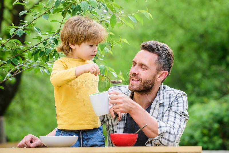 Carefree time together. happy fathers day. Little boy with dad eat cereal. father and son eating outdoor. summer picnic. Morning breakfast. family dinner time royalty free stock images