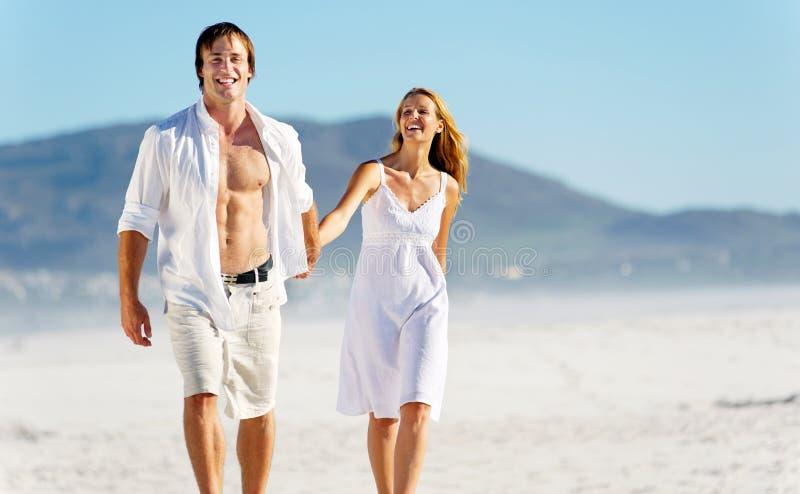 Carefree walking beach couple stock photo