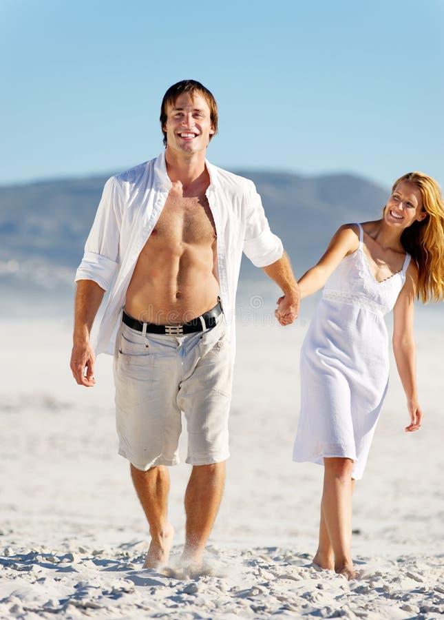 Carefree walking beach couple stock image