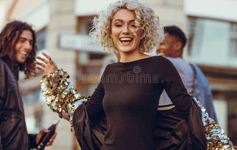 Carefree woman with friends on street. Beautiful young women wearing fashionable clothes walking on street with friends. Cheerful women with friends on city stock photo