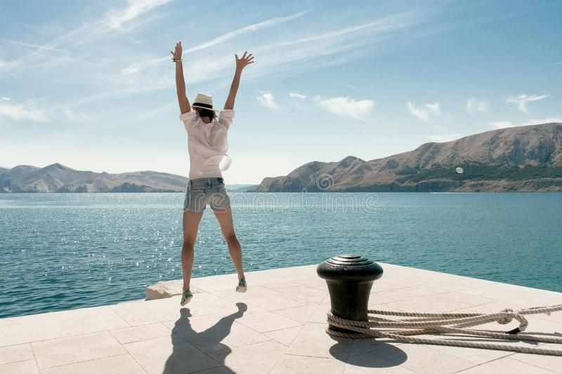 Carefree woman jumping at beach. Beautiful travel destination. Baska harbour, Krk island, Croatia. Summer vacation concept. Arms up in the sky stock photo