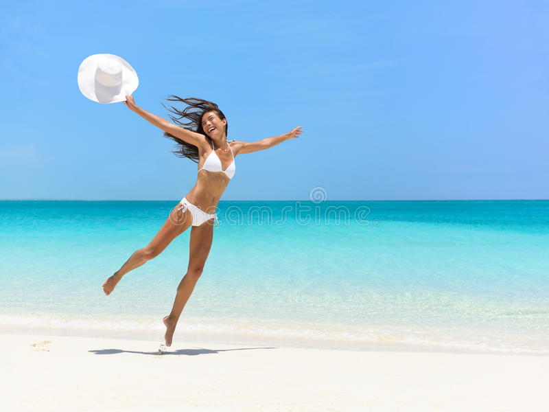 Carefree Woman Jumping At Beach During Summer stock image