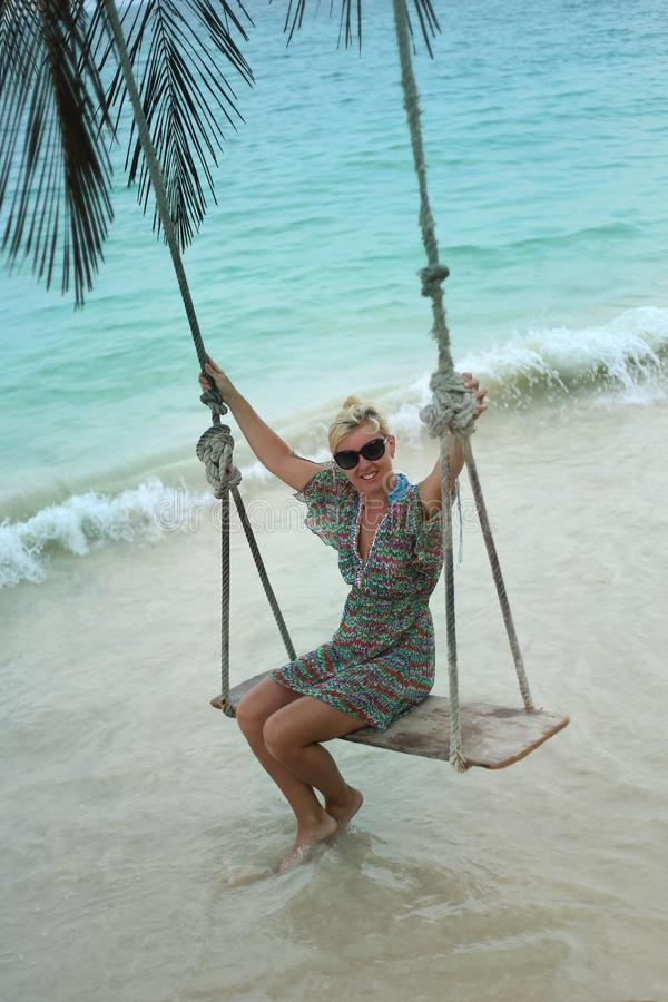 Carefree woman relaxing on tropical swing royalty free stock photos
