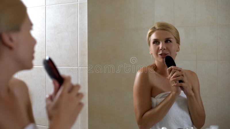 Carefree woman singing with hairbrush like with microphone, shattered dreams stock photo