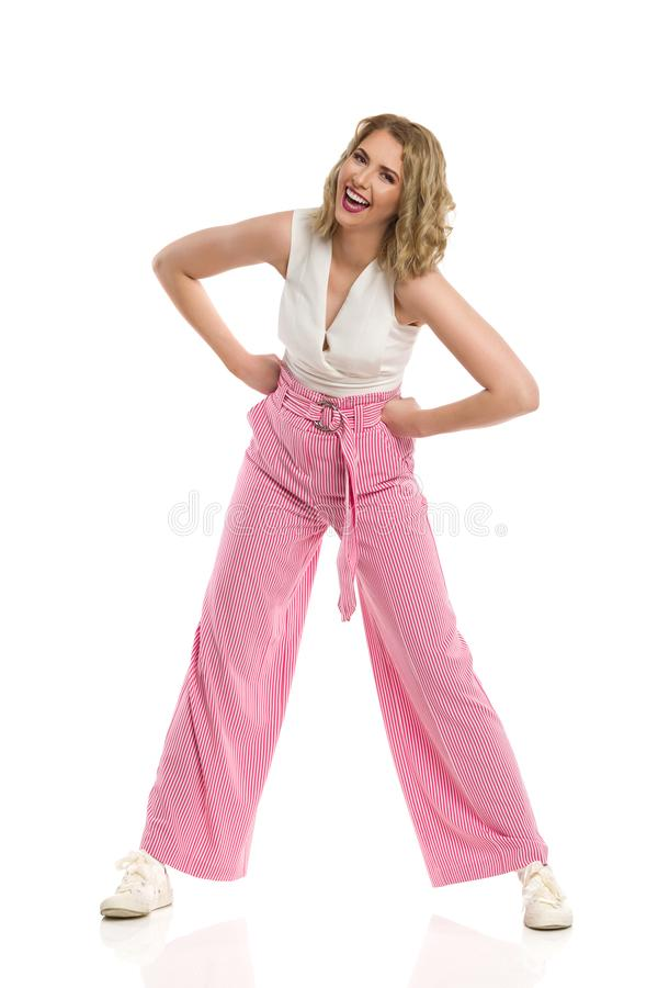 Carefree Woman In Striped Wide Legs Trousers Is Standing Legs Apart And Laughing stock photography