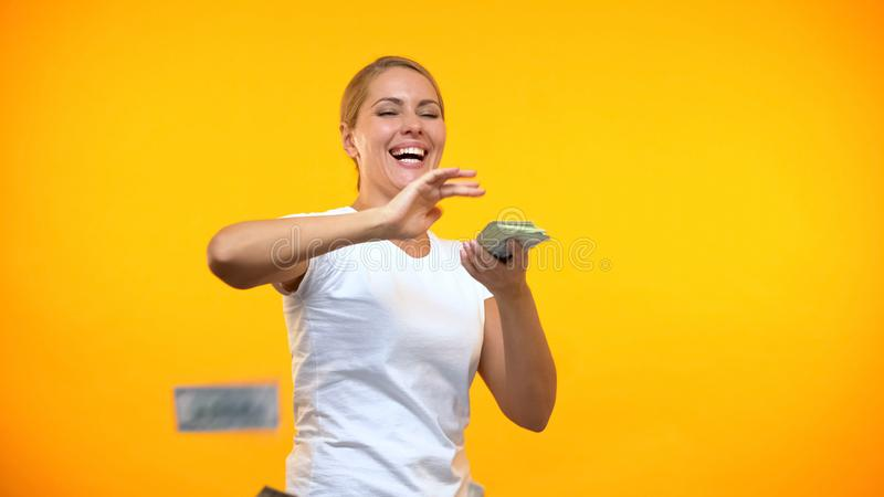 Carefree woman throwing dollars around, rich female wasting money, consumerism royalty free stock images