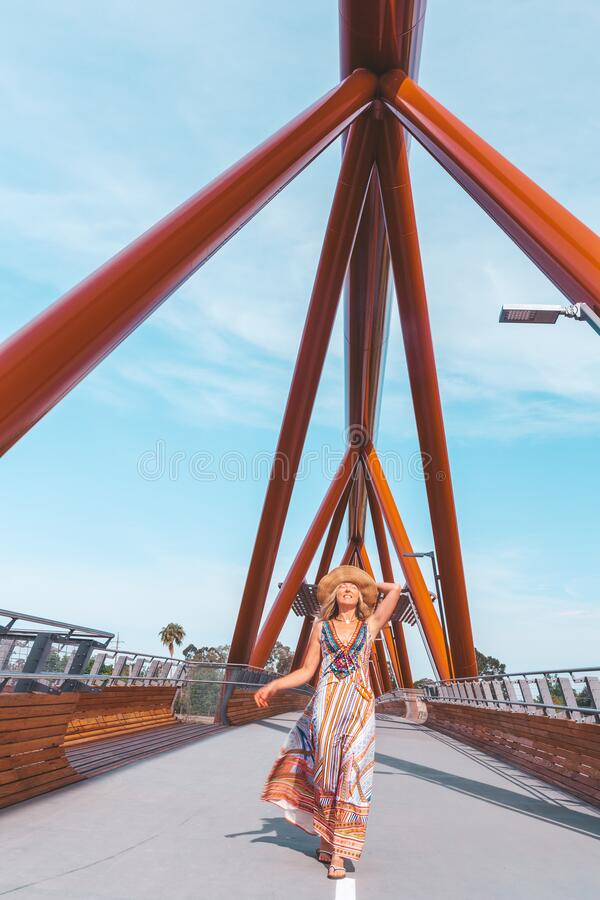 Carefree woman walking vicaciously across a modern bridge across the river stock images