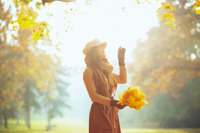 Carefree woman with yellow leaves outside in autumn park royalty free stock photo