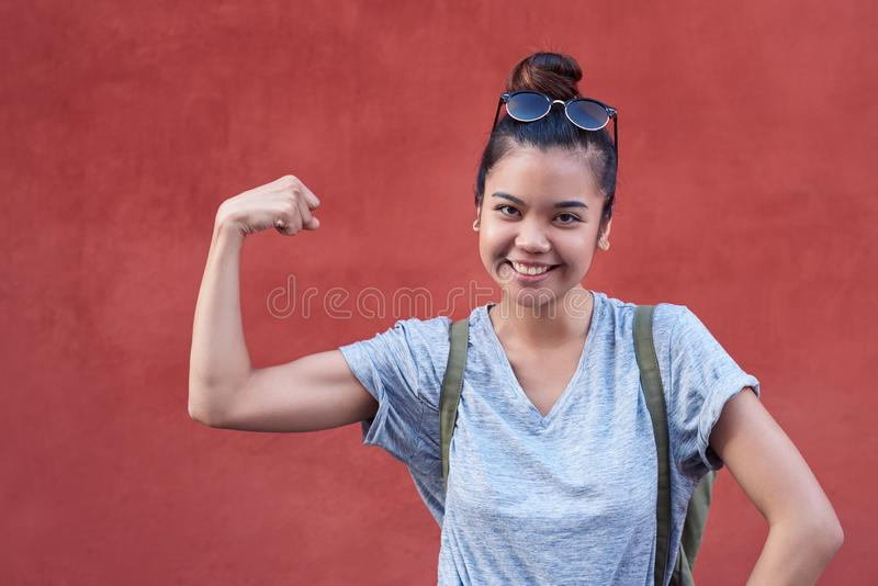 Young Asian woman smiling while humorously flexing her bicep outside stock photo