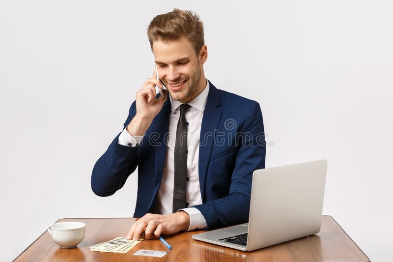 Carefree young confident, successful businessman sit office near laptop, drink coffee, talking to online shop manager stock photography