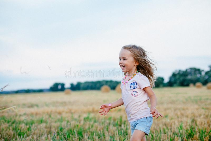 Carefree young girl in stubble field royalty free stock photo