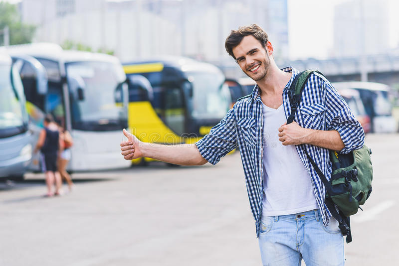 Carefree young man gesturing to stop car. Hitch-hiking. Happy male tourist is catching transport near bus station. He is looking forward and smiling royalty free stock photos