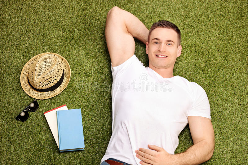 Carefree young man lying on grass stock image