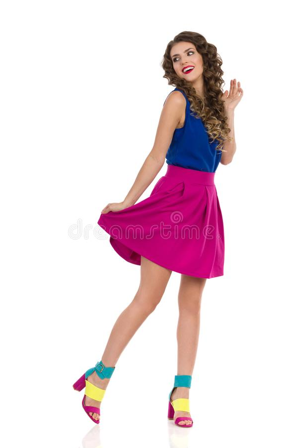 Carefree Young Woman In Colorful High Heels, Pink Mini Skirt And Blue Top Is Looking Away. Carefree young woman in colorful high heels, pink mini skirt and blue stock images