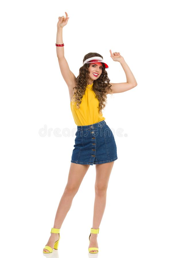 Carefree Young Woman In Jeans Mini Skirt And High Heels Is Standing With Arms Raised. Carefree young woman in jeans mini skirt, yellow top and high heels is stock photo