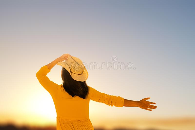 Carefree young woman looking at sunset. stock image