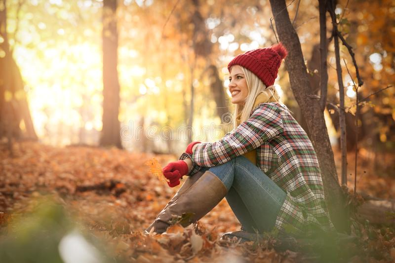 Carefree young woman in trendy clothes  sitting on yellow leafs in autumn park royalty free stock images