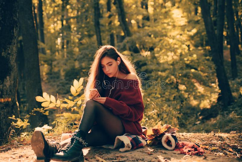 Carefree young woman in trendy vintage red pullover or sweater. Beautiful happy smiling girl with long hair wearing stock images