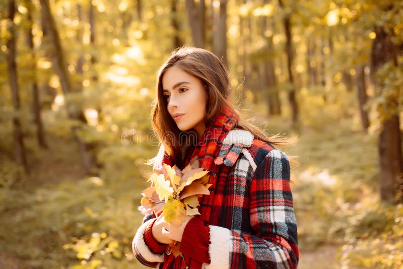 Carefree young woman in trendy vintage red pullover or sweater. Outdoor fashion photo of young beautiful lady surrounded royalty free stock photography