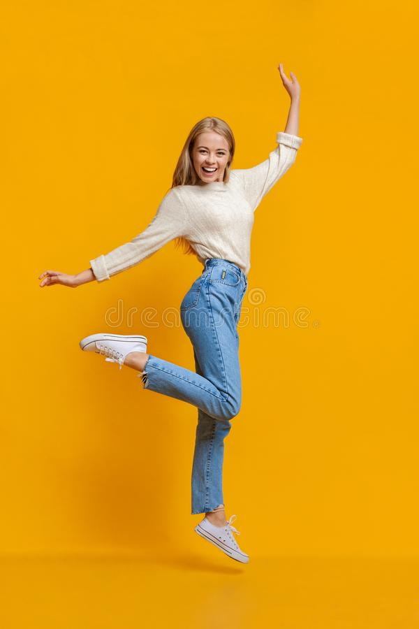 Carefree youth. Happy young girl jumping on air and smiling stock photos