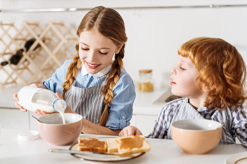 Careful adorable girl adding milk to her cereal stock image