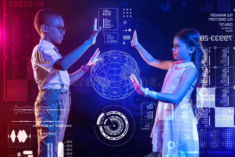 Careful kids making the hologram of the Earth while studying royalty free stock photos