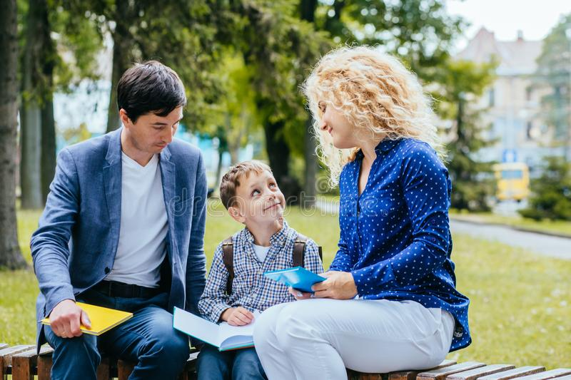 Careful mature parents helping child to learn new things. Family of three people sitting on bench in park reading book outdoor. Cheerful mature parents helping stock photo