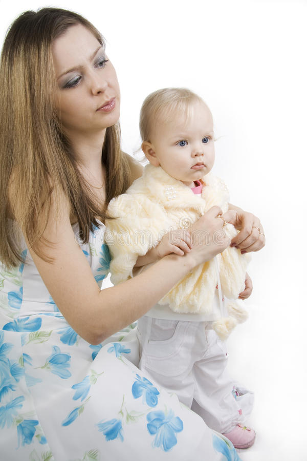 Careful mother dresses the daughter stock image