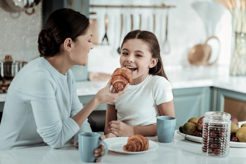 Careful mother feeding a kid with a croissant stock image
