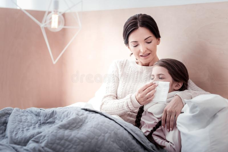 Careful mother lying in the bed with her ill child royalty free stock photo
