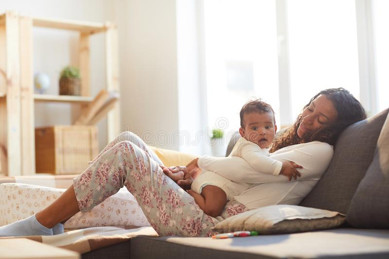 Careful mother relaxing with baby stock image