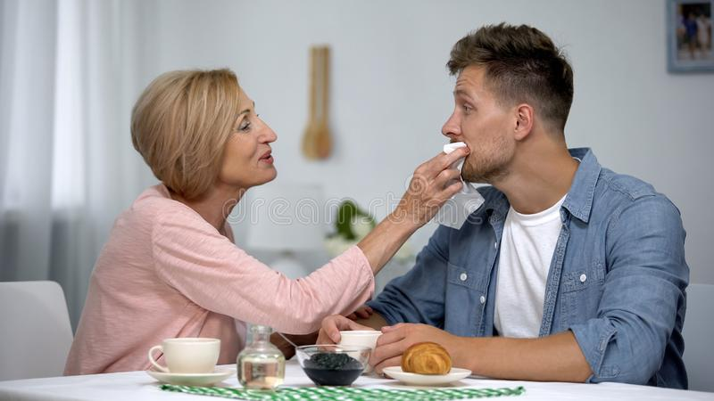 Careful mother wiping adult sons mouth during having tea at home, overprotection stock photography