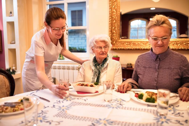 Careful nurse sets a table for dinner to patients at nursing home stock images
