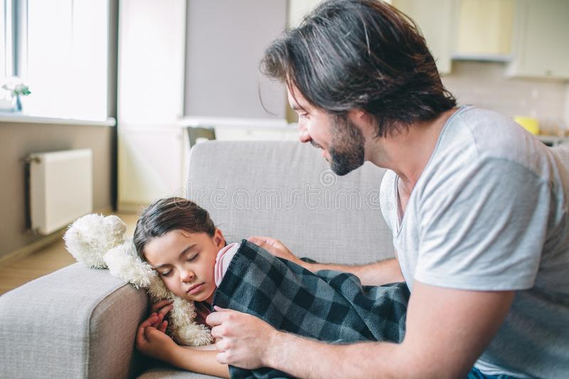 Careful parent is covering his daughter with blanket. She fell asleep. Guy looks at er and smiles. royalty free stock photo