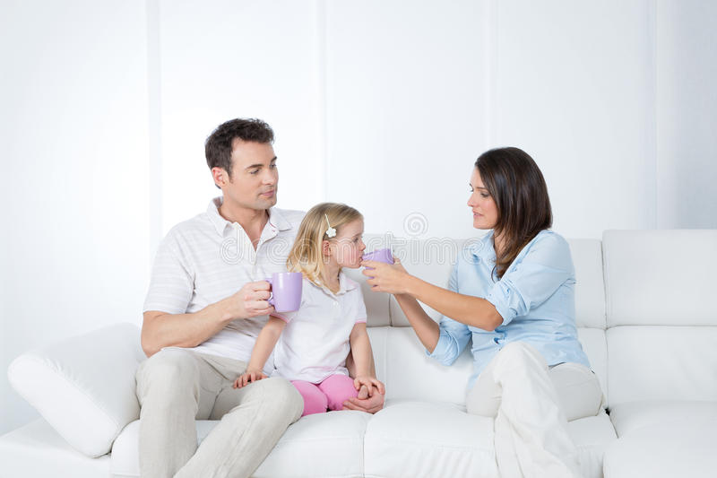 Careful parents with little daughter. Girl drinks hot infusion from lilac cup stock photos