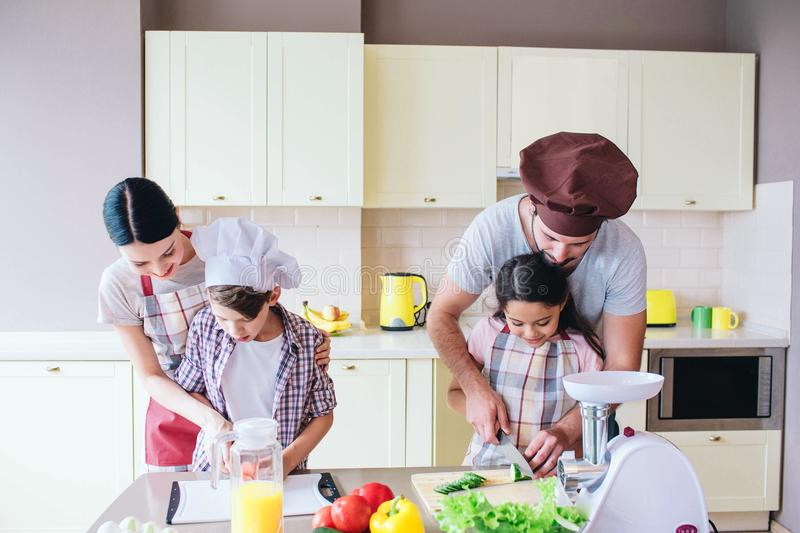 Careful parents are standing behind their kids and helping them to cut vegetables. They teach kids how to cut tomato and. Cucumber in a right way stock photos