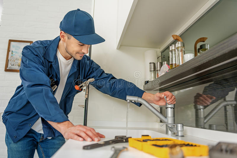 Careful smiling man in kitchen. Attentive repairman is opening modern crane. He looking at running water with smile royalty free stock photo