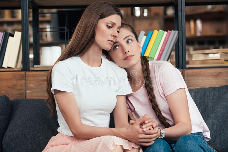 Careful teenage girl laying on shoulder of frustrated mother on sofa. At home stock images