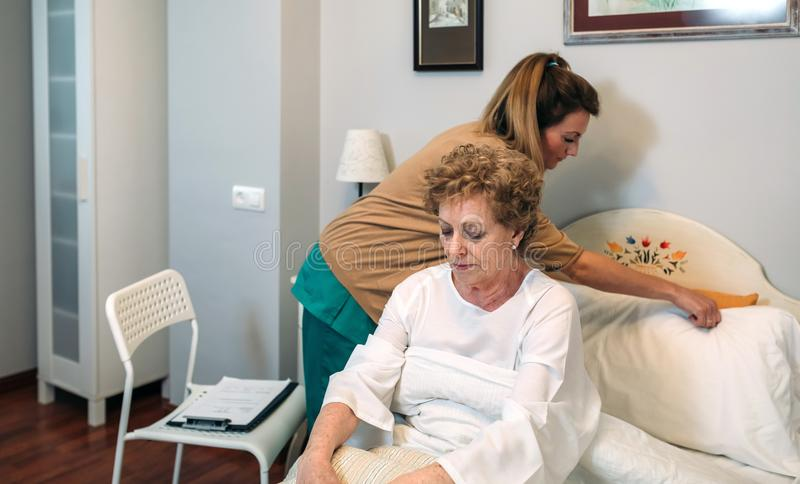 Caregiver accommodating pillow to elderly patient. Female caregiver accommodating the pillow to elderly female patient royalty free stock photography