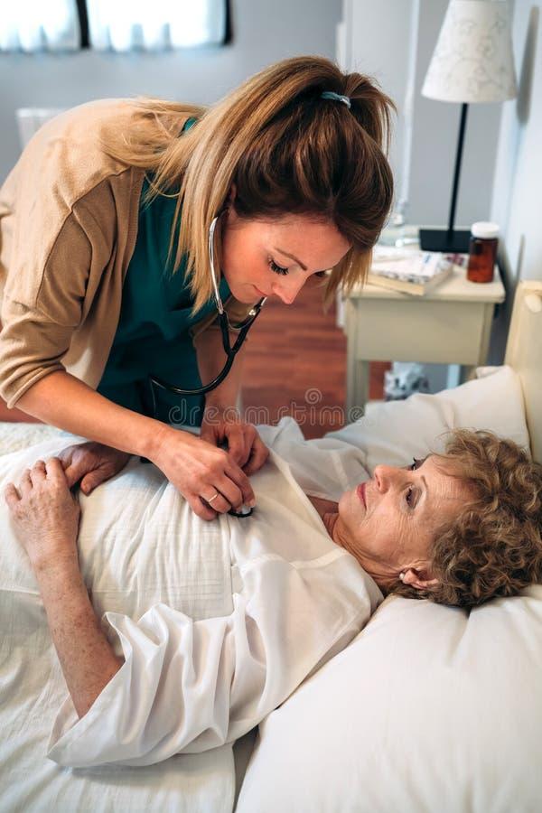 Caregiver auscultating senior woman. Female caregiver auscultating senior women at home stock photos