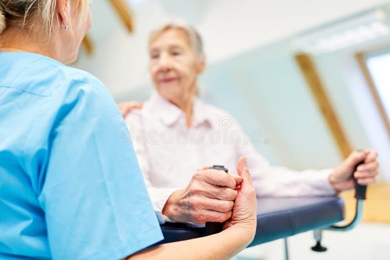 Caregiver cares and consoles senior woman stock photos