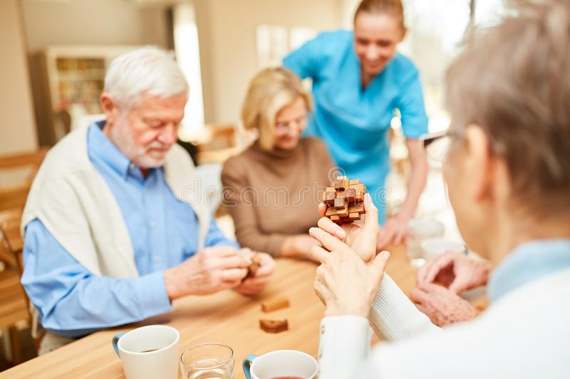 Caregiver cares for seniors in dementia therapy royalty free stock image