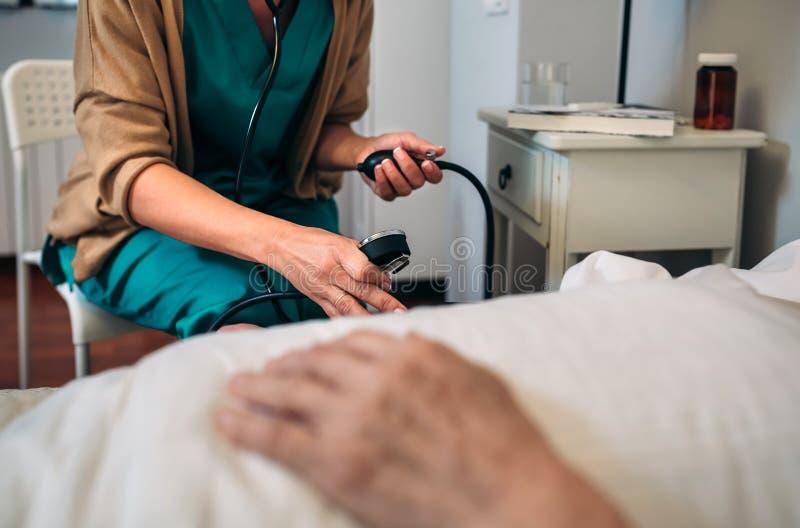 Caregiver checking blood pressure to a senior woman. Female caregiver checking blood pressure to a senior women at home stock photo