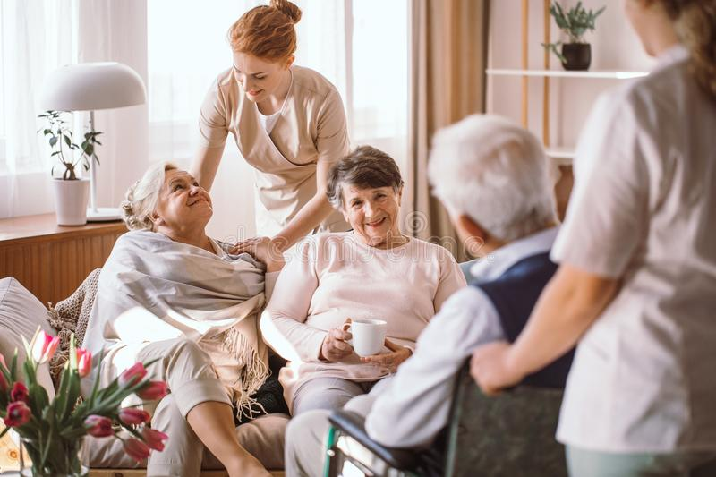 Young caregiver comforting elderly woman in nursing home. Caregiver comforting elderly women in nursing home royalty free stock photo