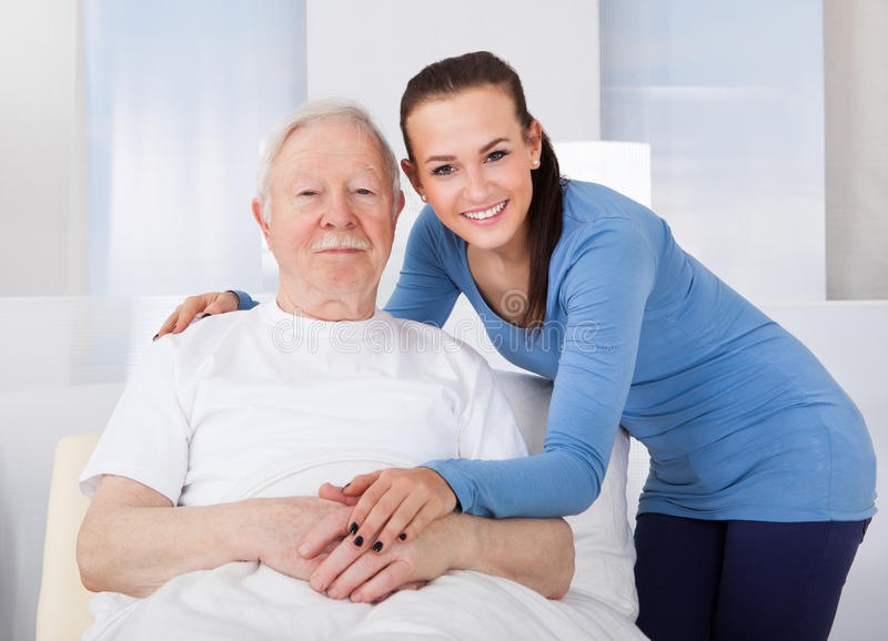 Caregiver consoling senior man. Young female caregiver consoling senior men at nursing home royalty free stock image
