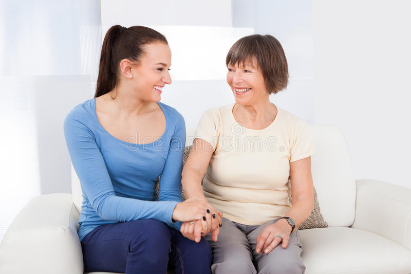 Caregiver consoling senior woman. Young female caregiver consoling senior women while sitting on sofa at nursing home royalty free stock photos
