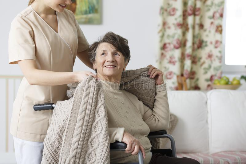 Caregiver covering senior woman with a blanket. Young caregiver covering senior women sitting on a wheelchair with a blanket stock photography